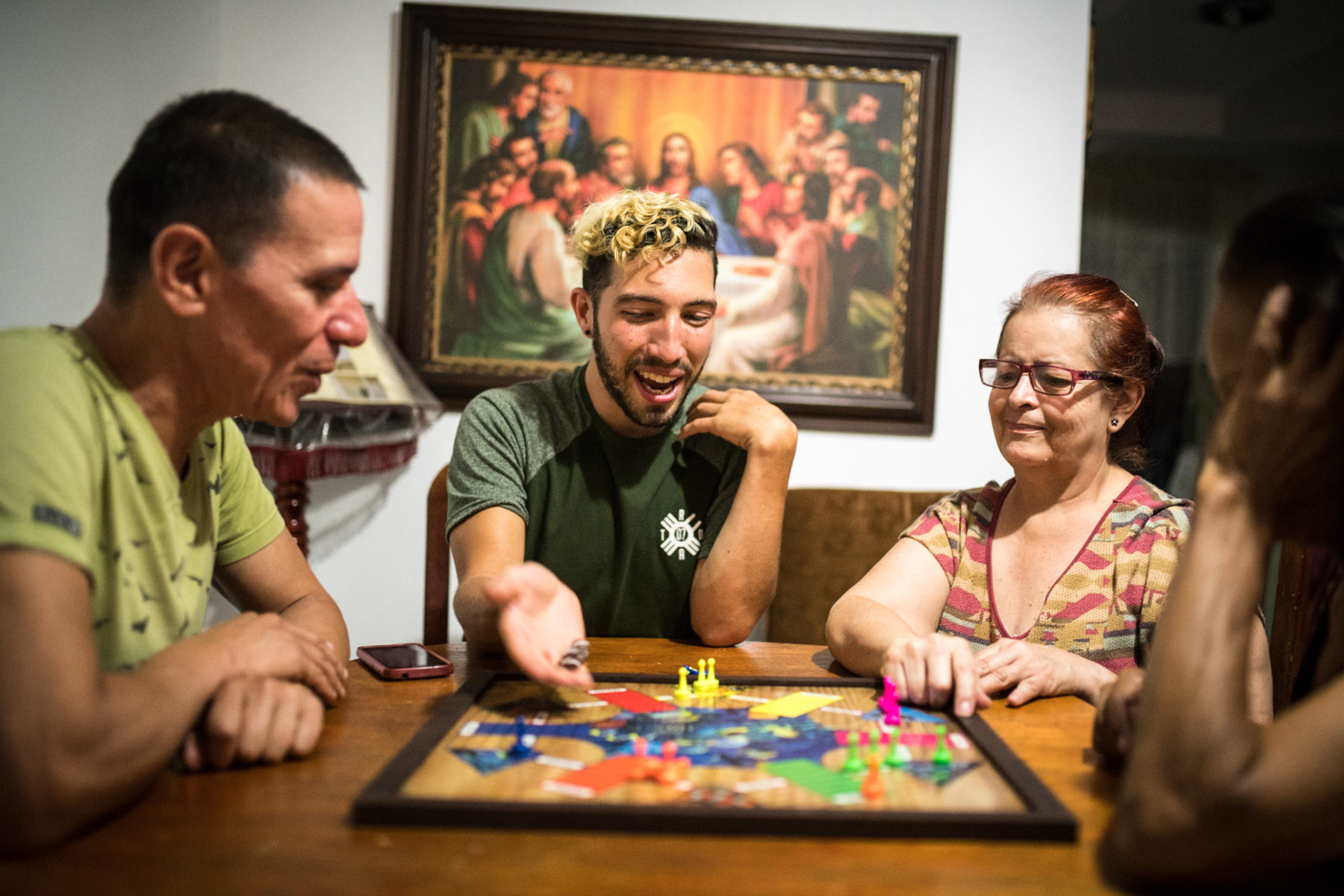 "Neighbor Ampario Osorio Rubiano is very Christian and has health problems. Victor and Manuel come by almost every day to play "" Parqués"" with her. Osorio likes all three men. During the game she ignores Manuel's curses and frivolous allusions and is happy about the company."